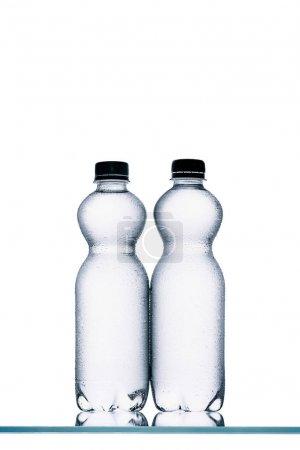 wet plastic bottles of water isolated on white