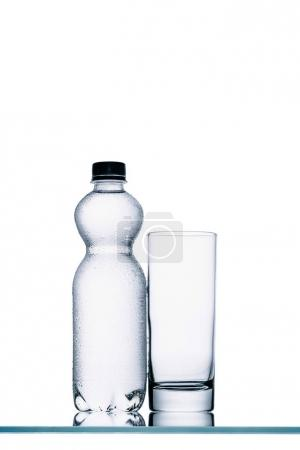 Photo for Full plastic bottle of water and empty glass isolated on white - Royalty Free Image