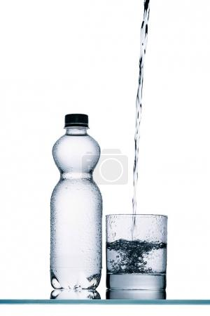 Photo for Wet plastic bottle and water pouring into glass isolated on white - Royalty Free Image