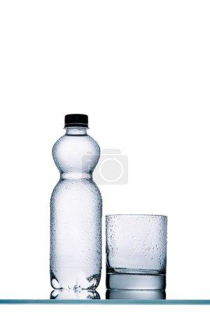 Photo pour Bouteille en plastique plein humide d'eau et de verre vide isolé sur blanc - image libre de droit