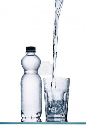 Photo for Plastic bottle and water pouring into glass isolated on white - Royalty Free Image