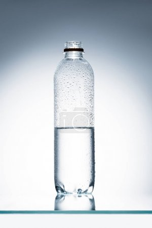 Photo for Half full plastic bottle of water on reflective surface - Royalty Free Image