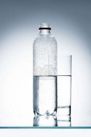 plastic bottle and glass of water on reflective surface