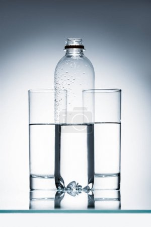 plastic bottle and glasses of clean water on reflective surface