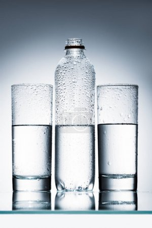Photo for Plastic bottle and glasses of clean water in row on reflective surface - Royalty Free Image