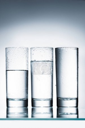 glasses of water in row of different levels on reflective surface