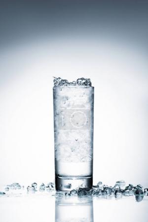 Photo pour Verre d'eau froide avec glace concassée sur surface réfléchissante sur blanc - image libre de droit