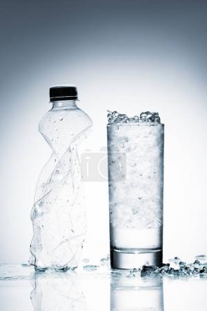 glass of cold water with ice and crumpled plastic bottle on reflective surface on white