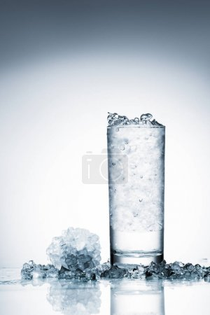 glass of cold water with ice on reflective surface on white