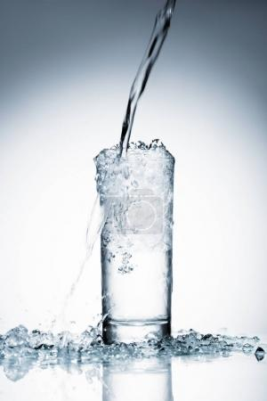 Photo for Close-up shot of water pouring into glass on white - Royalty Free Image