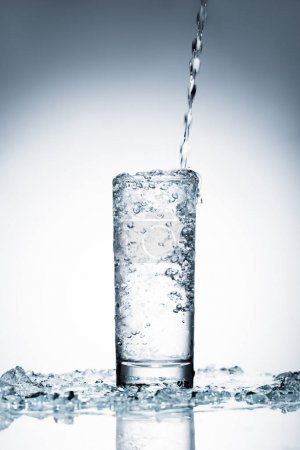 cold water pouring into glass on white