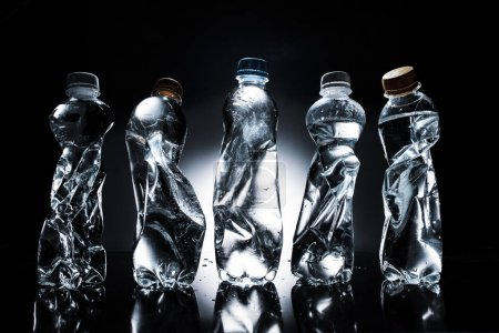 various crumpled plastic bottles of water in row on dark