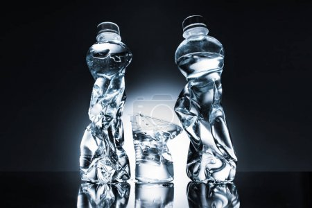 still life with crumpled plastic bottles and water and cup of water on dark