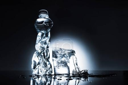 crumpled plastic water bottle and cup on dark