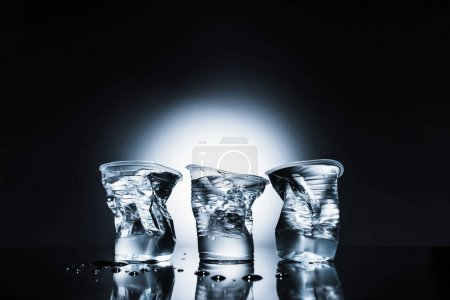 crumpled plastic cups of water on dark