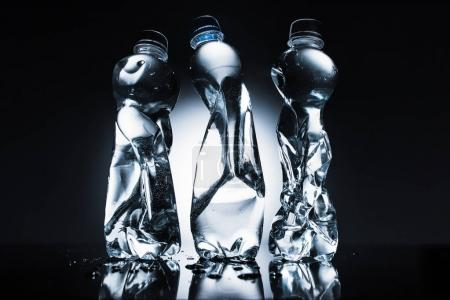 various crumpled bottles of water on dark