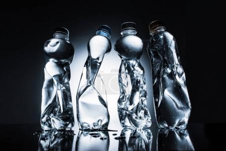 row of crumpled bottles of water on dark