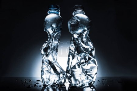 still life with crumpled bottles of water on dark