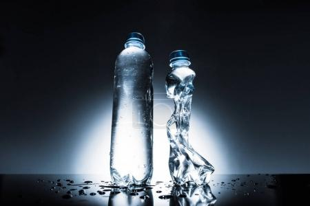 untouched and crumpled bottles of water on dark