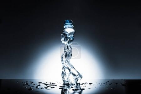crumpled plastic bottle of water on dark