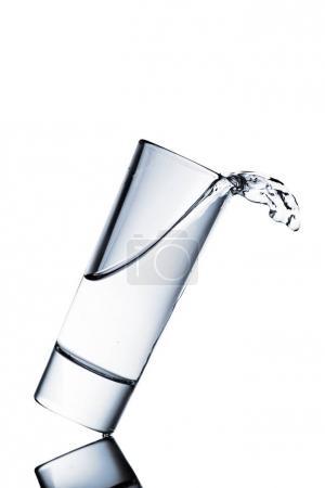 Photo pour Déversement d'eau à partir de verre isolé sur blanc - image libre de droit