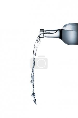 water pouring from glass bottle isolated on white