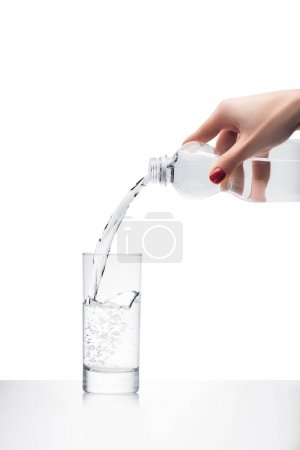 Photo for Cropped shot of woman pouring water into glass from plastic bottle isolated on white - Royalty Free Image