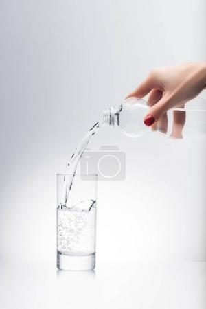 cropped shot of woman pouring water into glass from plastic bottle