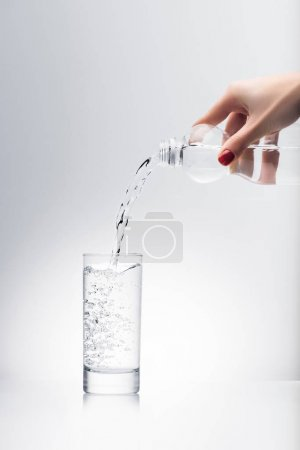 Photo for Cropped shot of woman pouring water into glass from plastic bottle - Royalty Free Image