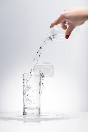 cropped shot of woman pouring fresh water into glass from plastic bottle