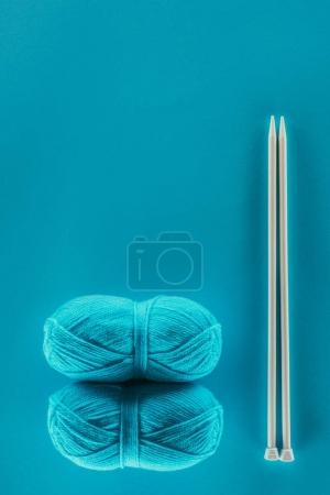 top view of blue knitting yarn balls with knitting needles, isolated on blue