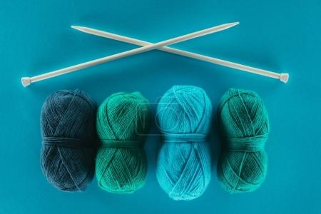top view of blue and green knitting yarn with knitting needles, isolated on blue
