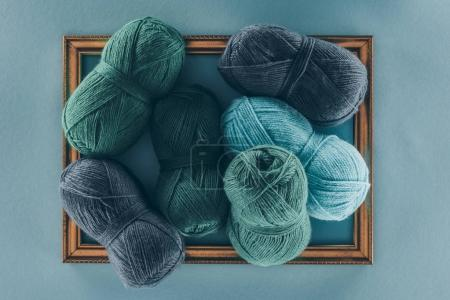 top view of blue and green knitting wool balls on frame, isolated on blue