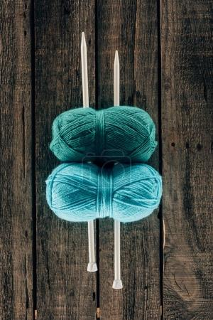 top view of blue and green yarn with knitting needles on wooden background