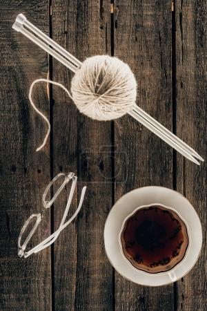 top view of knitting needles, yarn, cup of tea and eyeglasses on wooden background
