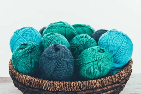 blue and green knitting wool balls in wicker basket on white