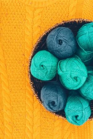 top view of blue and green knitting yarn balls in wicker basket on yellow knit