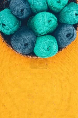 top view of blue and green knitting wool balls in wicker basket on yellow knit