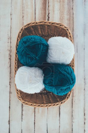 top view of white and blue knitting wool balls in wicker basket on wooden background