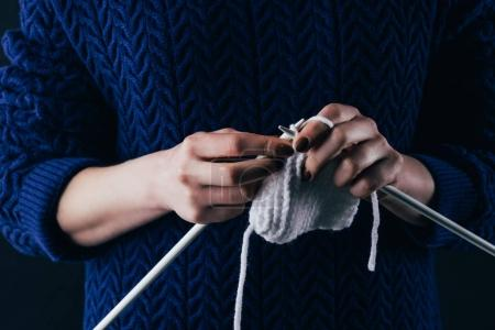 cropped view of woman knitting white wool with needles