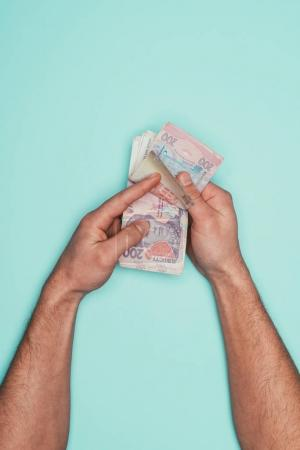 cropped shot of man counting cash isolated on turquoise