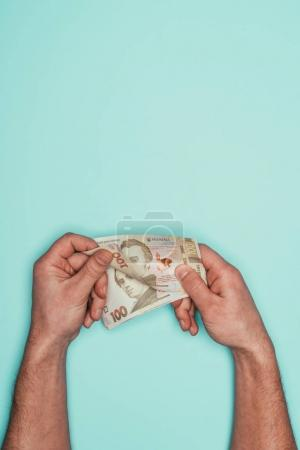 cropped shot of man counting money isolated on turquoise