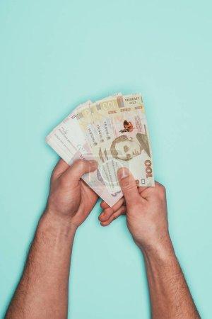 cropped shot of man holding bunch of ukrainian money isolated on turquoise