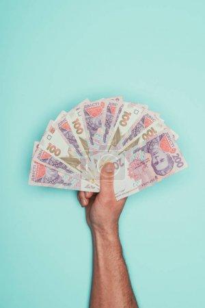 cropped shot of man holding bunch of ukrainian cash isolated on turquoise