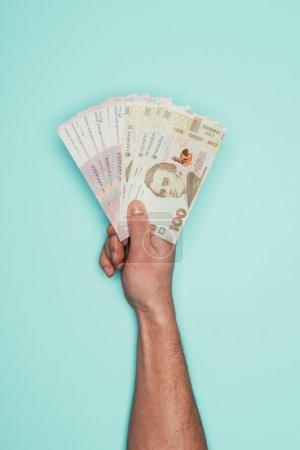 cropped shot of man holding ukrainian money isolated on turquoise