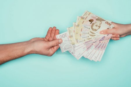 cropped shot of man taking money from woman isolated on turquoise