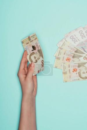 cropped shot of woman with ukrainian money isolated on turquoise