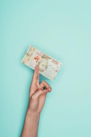 cropped shot of woman holding ukrainian money isolated on turquoise