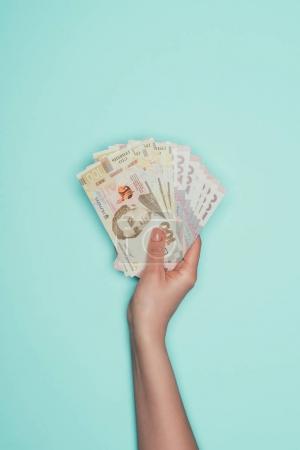 cropped shot of holding bunch of ukrainian cash isolated on turquoise