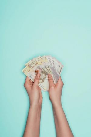 cropped shot of holding bunch of ukrainian cash in hands isolated on turquoise